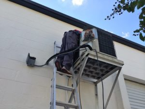 Coolco employee on a ladder servicing an elevated AC unit